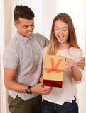 Young Beautiful Woman opening Present of her Handsome man Royalty Free Stock Image