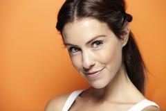 Young beautiful woman, on orange background Royalty Free Stock Image