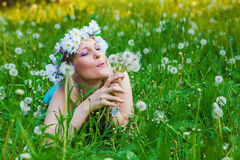Young woman blowing a dandelion on fields Royalty Free Stock Photos