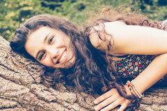Young beautiful woman over a trunk Royalty Free Stock Images