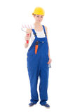 Young beautiful woman painter in blue coveralls and yellow helme Stock Images