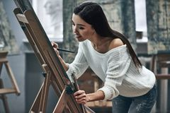 Artist painting. A young beautiful woman is a painting artist while working in a studio royalty free stock photography