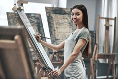 Artist painting. A young beautiful woman is a painting artist while working in a studio royalty free stock image