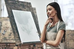Artist painting. A young beautiful woman is a painting artist while working in a studio stock photo