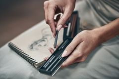 Artist painting. Young beautiful woman painting artist while working in studio, hands close-up royalty free stock images
