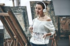 Artist painting. Young beautiful woman painting artist while working in studio, listening to music in headphones royalty free stock photos
