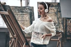 Artist painting. Young beautiful woman painting artist while working in studio, listening to music in headphones stock image