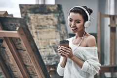 Artist painting. Young beautiful woman painting artist while working in studio, listening to music in headphones stock photo