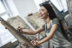 Artist painting. Young beautiful woman painting artist while working in a studio, smiling to the camera stock images
