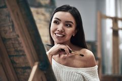 Artist painting. Young beautiful woman painting artist while working in a studio, smiling to the camera royalty free stock photo