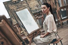 Artist painting. Young beautiful woman painting artist while working in a studio, smiling to the camera royalty free stock photos