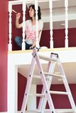 Young beautiful woman painting a ledge ballustrade white with a brush. New home, new living room, house improvement, home renovation stock photos