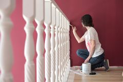Young beautiful woman painting a ledge ballustrade white with a brush. New home, new living room, house improvement, home renovation stock photography