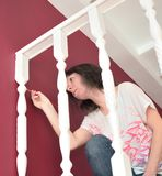 Young beautiful woman painting a ledge ballustrade white with a brush royalty free stock photography