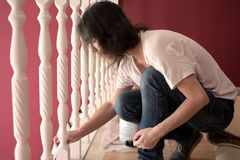 Young beautiful woman painting a ledge ballustrade white with a brush. New home, new living room, house improvement, home renovation royalty free stock images