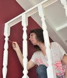 Young beautiful woman painting a ledge ballustrade white with a brush. New home, new living room, house improvement, home renovation royalty free stock image
