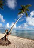The young beautiful woman and palm tree on seacoast against the cloudy sky Stock Photography