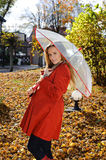 Young beautiful woman in the park in a fashion shot, looking away and smiling - caucasian woman, autumn, fall, park, umbrella Royalty Free Stock Image