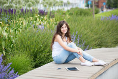 Young beautiful woman in the park with gadgets Stock Images