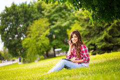 Young beautiful woman in the park with gadgets Royalty Free Stock Photo