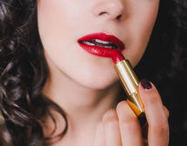 Young beautiful woman with perfect skin using red lipstick Royalty Free Stock Images