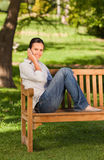 Young beautiful woman phoning on the bench Stock Image