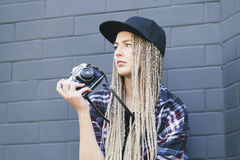 Young beautiful woman photographer is holding the camera. And looking away. She has got long blond hair, full lips and green eyes Royalty Free Stock Images