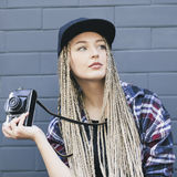 Young beautiful woman photographer is holding the camera. And looking away. She has got long blond hair, full lips and green eyes Royalty Free Stock Photos
