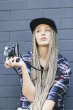 Young beautiful woman photographer holds the camera. Young beautiful woman photographer is holding the camera and looking away. She has got long blond hair, full Stock Image