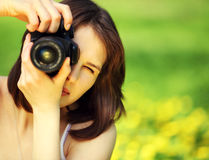 Young beautiful woman photographing in summer park Stock Photography