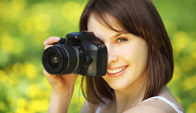 Young beautiful woman photographing in summer park Royalty Free Stock Image