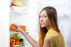 Young beautiful woman picking food from fridge Royalty Free Stock Photography
