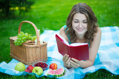 Young beautiful woman with picnic basket and fruits reading book Royalty Free Stock Images