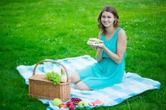 Young beautiful woman with picnic basket, fruits and sandwiches Royalty Free Stock Photography
