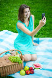 Young beautiful woman with picnic basket and fruits using smart Royalty Free Stock Photos