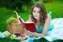 Young beautiful woman with picnic basket lying and reading book Stock Photo