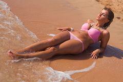Young beautiful woman in pink bikini laying. On sand beach Royalty Free Stock Photography