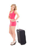 Young beautiful woman in pink dress with suitcase on white backg Royalty Free Stock Image