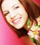 Young beautiful woman with pink flower Royalty Free Stock Photo