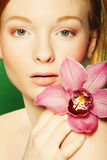 Young beautiful woman with pink flower Royalty Free Stock Image