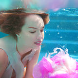 Young beautiful woman with pink flower underwater Stock Photos