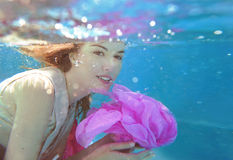 Young beautiful woman with pink flower underwater Stock Photo
