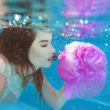 Young beautiful woman with pink flower underwater Royalty Free Stock Photography