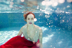 Young beautiful woman with pink flower underwaterSmiling young beautiful woman underwater Royalty Free Stock Image