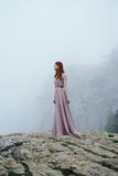 Young beautiful woman in pink long dress at the edge of a mountain cliff near the fog.  Royalty Free Stock Photography