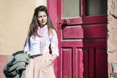 Young beautiful woman with pink scarf against pink  door Stock Photography