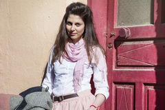 Young beautiful woman with pink scarf against pink  door Stock Photos