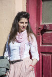 Young beautiful woman with pink scarf against pink  door Stock Image
