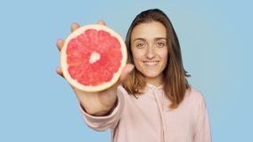Cute happy smiling woman holds pink grapefruit stock video