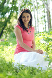 Young Beautiful woman in pink top sitting outdoors Stock Photo